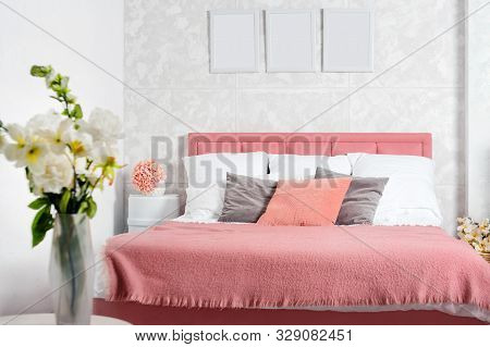 Stylish Interior Of Modern Bedroom. White And Pink Design Of Cozy Bedroom With Flowers. King-size Be