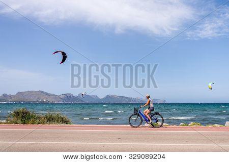 Kite Surfing In Pollenca, Majorca, Spain. Woman Riding A Bike.