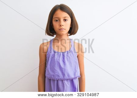 Young beautiful child girl wearing purple casual dress standing over isolated white background with serious expression on face. Simple and natural looking at the camera.