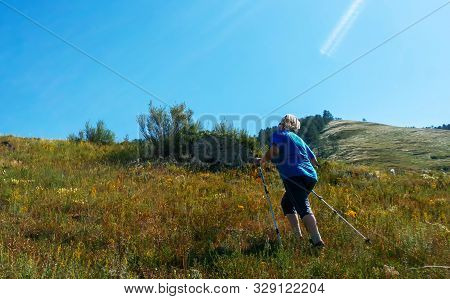 A Grown Woman On A Walk With Nordic Walking Sticks. The Concept Of A Healthy Lifestyle At Any Age.