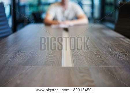 Employee In Office Conference Room. Manager At Table In Modern Meeting Room For Business Negotiation