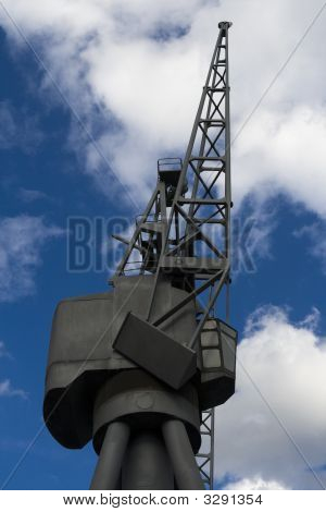 Looking Up At Old Dockside Crane With Blue Sky Background