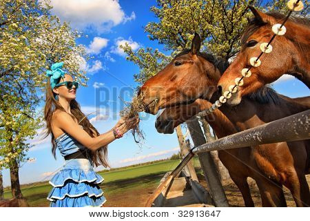Beautiful girl feeding her horses at ranch poster