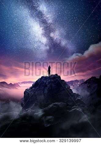Night Sky Long Exposure Landscape. A Man Standing On A High Rock Watching The Stars Rise Into The Ni