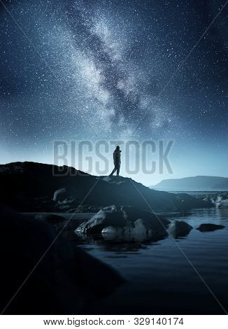 Calm Midnight Adventures. A Long Exposure Shot Of A Man Staring Up Into The Night Sky, Silhouetted A