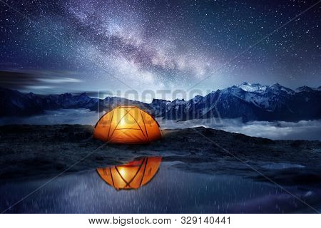 Camping Adventure In The Mountains. A Tent Pitched Up And Glowing Under The Milky Way. Photo Composi