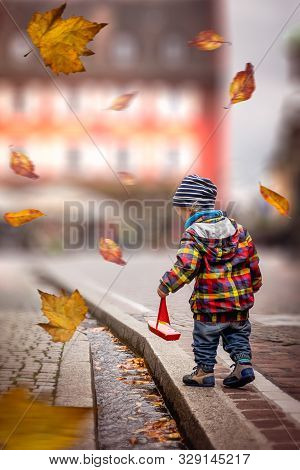 Child Playing With Boat In Autumn. Child In Colored Jacket Playing On Street In Autumn. Children In