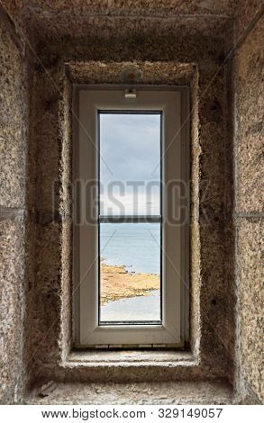 A Vertical View Of The Ocean Through A Lighthouse Window In The Stone Staircase