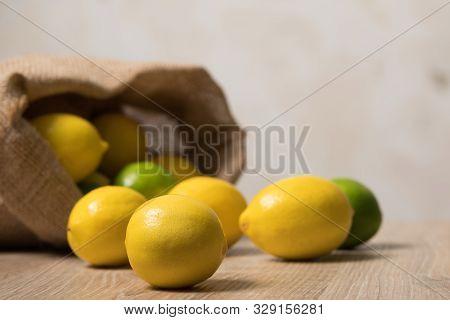 Lemons Image. Bag Of Lemons And Lime. Fabric Bag With Lemons. Full Sack Of Lemons On A Wooden Backgr
