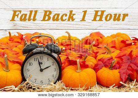Fall Back 1 Hour Time Change Message With A Retro Alarm Clock With Orange Pumpkins With Fall Leaves