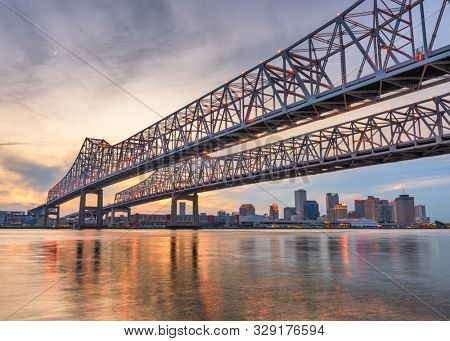 New Orleans, Louisiana, USA at Crescent City Connection Bridge over the Mississippi River at dusk.