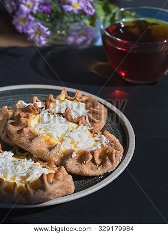 Karelian Pirakka Pies Located On A Gray Plate On A Black Stone Background. Near A Cup Of Tea. Tradit