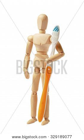 Oral Hygiene And Dental Care. Wooden Man Holds Toothbrush And Toothpaste.