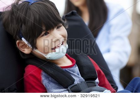Happy Five Year Old Disabled Boy In Wheelchair And Protective Gear