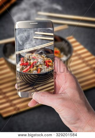 Man Taking Photo Of Asian Rice With Beef In Black Plate With Chopsticks On Dark Stone Table