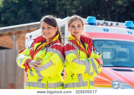 Paramedic and emergency doctor standing proud in front of ambulance