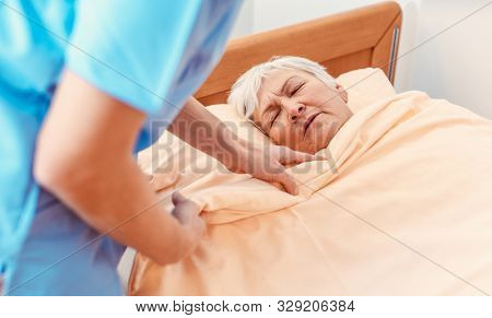 Caregiver pulling blanket over sleeping senior in pensioners home for better sleep