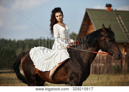 Girl In A Long Dress Riding A Horse, A Beautiful Woman Riding A Horse In A Field In Autumn. Country