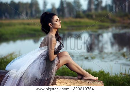 Girl In A Long Dress Near The Lake Sits On An Old Boat, A Beautiful Woman In The Rays Of The Evening