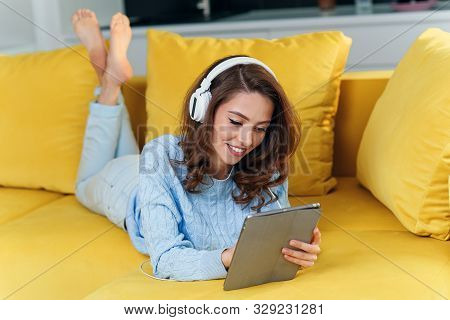Exuberant Happy Woman Uses Tablet Pc While Laying On The Comfortable Yellow Sofa And Listens To Musi