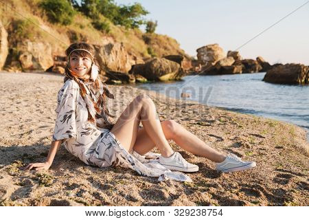 Image of beautiful hippy girl in feather headband sitting on sand by seaside in morning