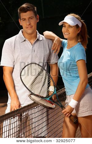 Attractive young couple standing on tennis court, smiling.