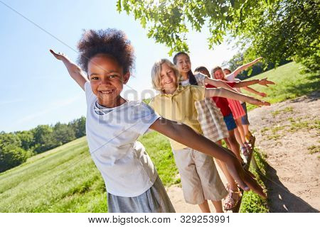 Multicultural kids balancing in the park for balance and fitness