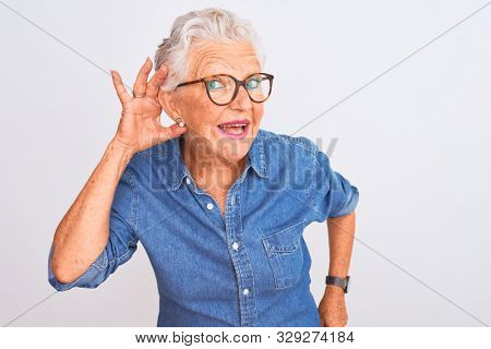 Senior grey-haired woman wearing denim shirt and glasses over isolated white background smiling with hand over ear listening an hearing to rumor or gossip. Deafness concept.
