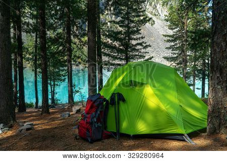 Camping Site In The Woods By The Lake, Green Tent And Backpack.