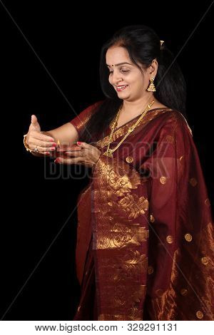 A Middleaged Indian Woman Smiling At Her Traditional Diwali Lamp And Protecting It From Getting Esti