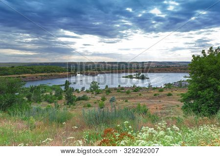 Scenic View On Flooded Quarry With Blue Water Under Cloudy Sky With Green Fields And Trees Around It