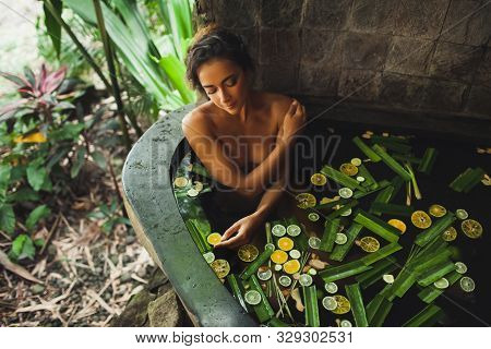 Beautiful Young Woman Enjoying In Outdoor Spa. Luxury Stone Bath Tub With Jungle View. Natural Organ