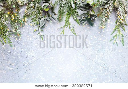 Christmas or winter background with a border of green and frosted evergreen branches on a grey vintage board. Flat lay, winter concept with copy space.