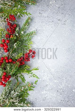 Christmas or winter background with a border of green and frosted evergreen branches and red berries on a grey vintage board. Flat lay, winter concept with copy space.