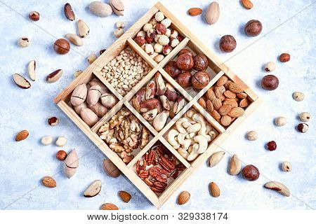 Assortment Of Nuts In A Wooden Box, On A Blue Background. Pecans, Hazelnuts, Almonds, Pine Nuts, Bra