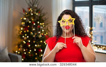 party, celebration and holidays concept - funny woman with star shaped glasses and red lips over christmas tree lights on home background