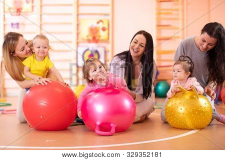 Mothers With Their Babies Doing Exercises With Gymnastic Ball At Fitness Class. Concept Of Caring Fo