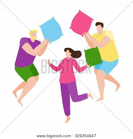 Young People Having Fun At A Pajama Sleepover Party. Two Guys And A Girl Fight With Pillows. Colorfu