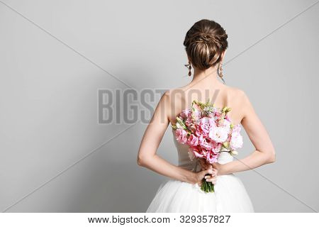 Beautiful Young Bride With Wedding Bouquet On Grey Background,  Back View