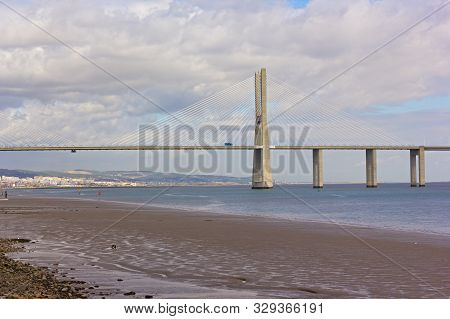 Vasco Da Gama Bridge With The Capital City On Horizon In Lisbon, Portugal. Colorful Patterns On Tagu