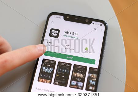 Warsaw, Poland - October 22, 2019: User Installing Hbo Go Film Streaming App On A Xiaomi F1 Pocophon