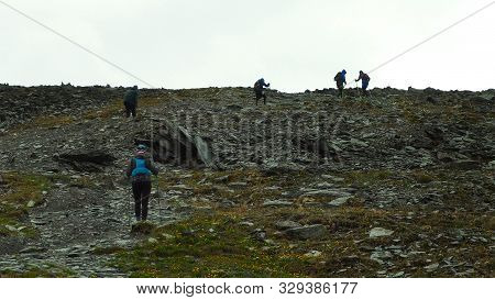 Group Ultra Trail Running With Trekking Poles In Mountain Road. Difficult Stone Path To The Top.