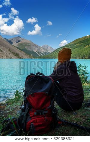 A Young Girl In Knitted Hat With A Backpack Relaxes On The Shore Of A Beautiful Lake And Looks At Th