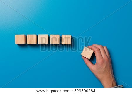 Woman's Hand Establishes A Wooden Cubes In Row. Blank Wooden Blocks For Word, Text Or Illustration.