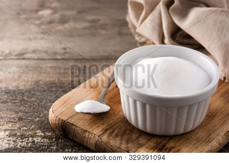 Baking Soda In White Bowl On Wooden Table. Copy Space