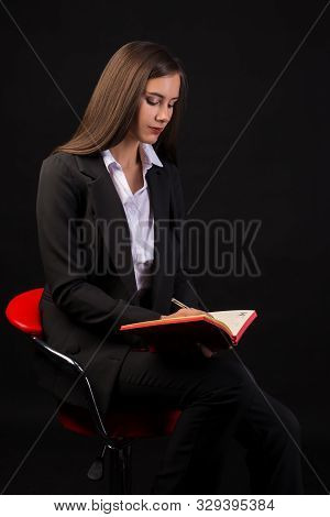 Young Beautiful Girl Sitting On Red Chair With Red Notepad In Hands Black Background, Business Lady,