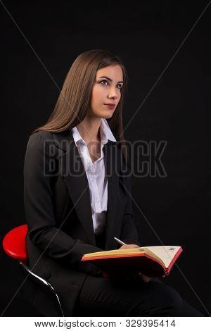 Young Beautiful Businesswoman Girl Sitting On Chair With Red Notebook On Dark Background In Business
