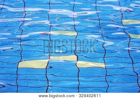 Pure Blue Water In The Pool. Water Background. Swimming Pool Bottom Caustics Ripple And Flow With Wa