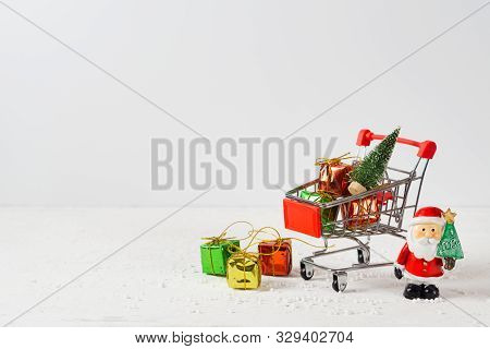 Shopping Cart With Christmas Tree And Miniature Gift Boxes And Santa Clause On Wooden Table. Christm