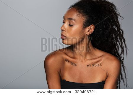 Picture of a pretty african woman isolated over grey wall background with my body my rules inscriptions on clavicles.